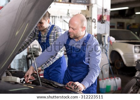 Happy male workers in overalls working in the garage. - stock photo