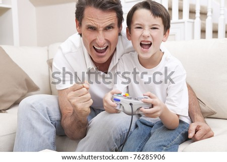 Happy man and boy, father and son, having fun playing video console games together, the young boy has the handset controller while dad is cheering. - stock photo
