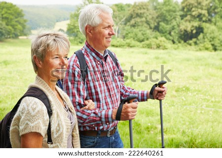 Happy man and elderly woman hiking together in summer - stock photo