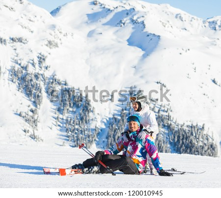 Happy man and his daughter sitting on top of Alps, resting after skiing against wonderful winter mountains background - stock photo