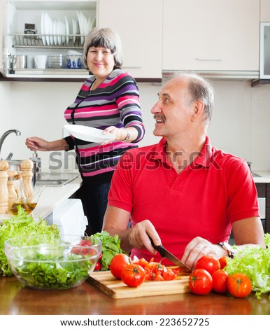 happy  man and mature woman  doing housework together in home kitchen