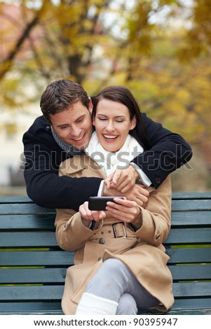 Happy man and smiling woman looking at a smartphone - stock photo