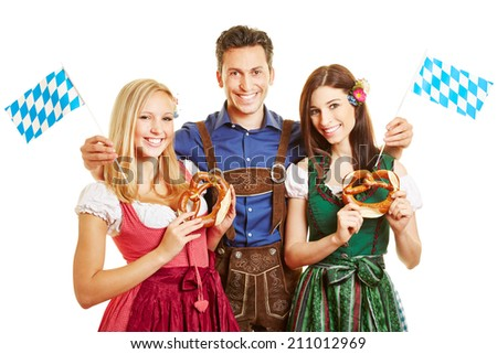 Happy man and two smiling women in traditional bavarian outfit with dirndl and leather pants - stock photo