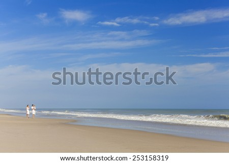 Happy Man and woman boy child couple family in white clothes walking on a deserted empty tropical beach with bright clear blue sky  - stock photo