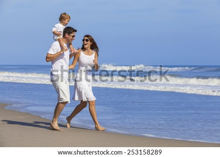 Happy Man and woman boy child couple family in white clothes walking playing on a deserted empty tropical beach with bright clear blue sky  - stock photo