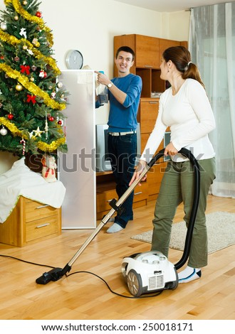 Happy man and woman cleaning with vacuum cleaner in Christmas time - stock photo