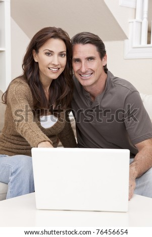 Happy man and woman couple in their thirties, sitting together at home on a sofa using a laptop computer - stock photo