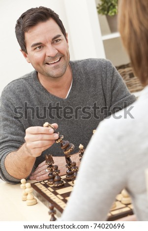 Happy man and woman couple in their thirties, sitting together at home playing chess - stock photo