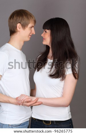 Happy man and woman dressed in white shirts holding hands and looking at each other on gray background