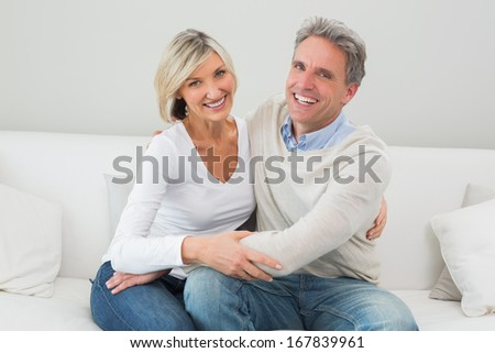 Happy man and woman embracing while sitting on sofa in living room at home