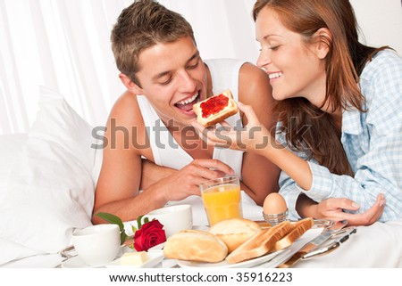 Happy man and woman having luxury hotel breakfast in bed together - stock photo