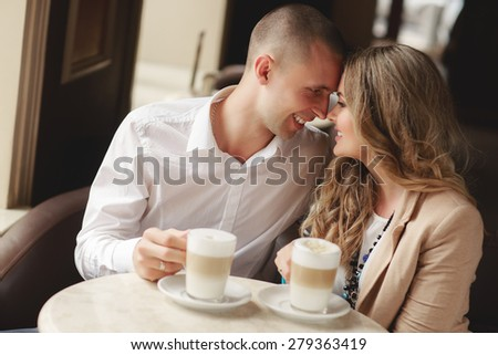 Happy man and woman in cafe. Loving couple on date at cafe. Two people in cafe enjoying the time spending with each other. Couple in cafe drinking coffee latte and smiling. Happy couple