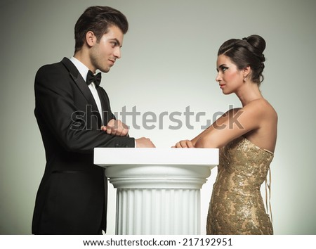 happy man and woman in evening clothes lean on a column and look at each other in studio - stock photo
