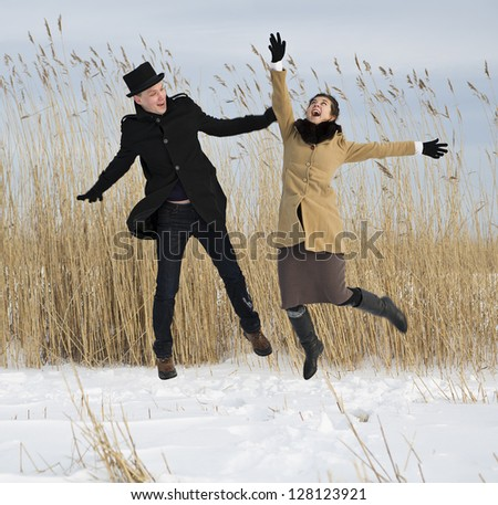 Happy man and woman jump on lake beach