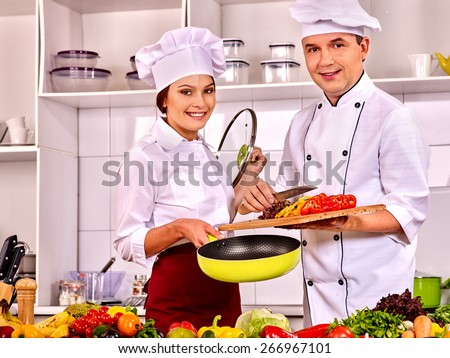 Happy man and woman professional in chef hat cooking chicken. - stock photo
