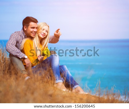 Happy man and woman seating on the seashore - stock photo