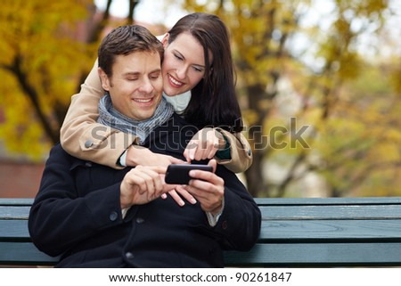 Happy man and woman using smartphone in autumn park