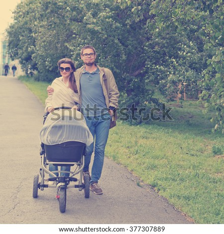 happy man and woman walking with baby pram outdoors. Instagram style filtred image