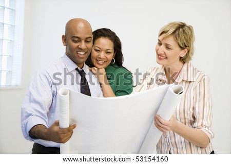 Happy man and women looking at architecture plans smiling. - stock photo