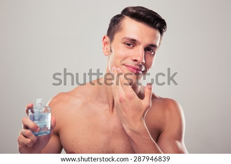 Happy man applying lotion after shave on face over gray background - stock photo