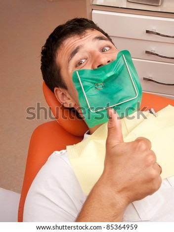 Happy man at the dentist's surgery. - stock photo