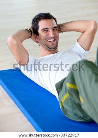 Happy man at the gym doing abdominals - stock photo