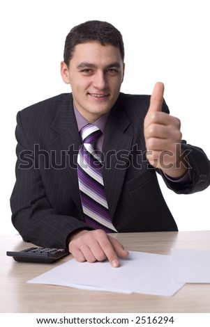 Happy man at the office desk. There are papers and a calculator on the  desk. Isolated on white in studio. - stock photo
