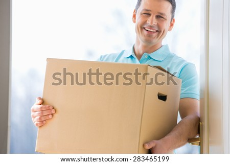 Happy man carrying cardboard box at entrance of new house - stock photo