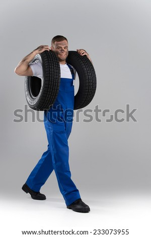 happy man carrying tire on grey background. studio shut of girty guy looking into camera and carrying wheel - stock photo