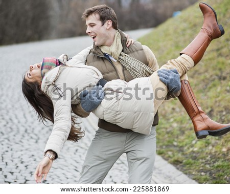 Happy man carrying woman in park - stock photo