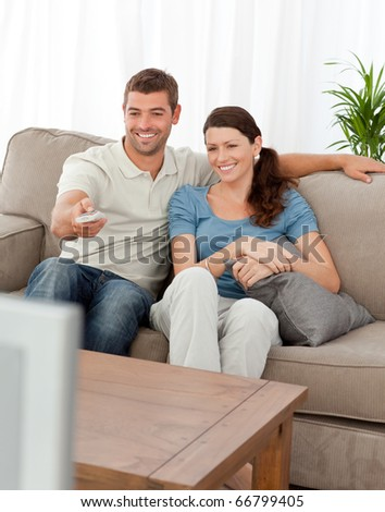 Happy man changing channel while watching television with his wife at home - stock photo