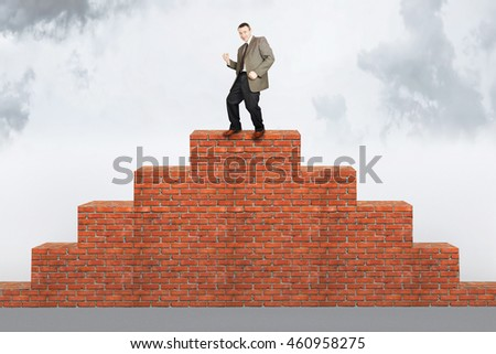 Happy man climbed on the brick pyramid. Concept of success