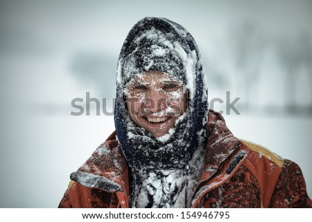 Happy man covered by snow enjoying winter.