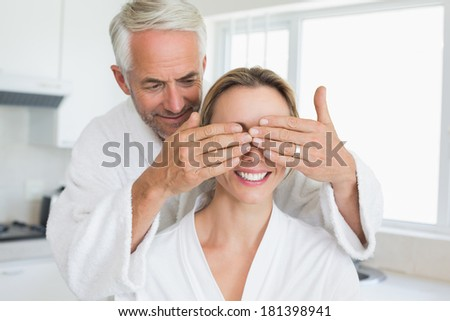 Happy man covering his partners eyes in the morning at home in the kitchen - stock photo