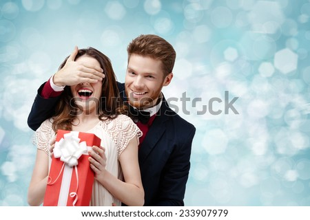 Happy man covers with hand eyes of his girlfriend, blue background