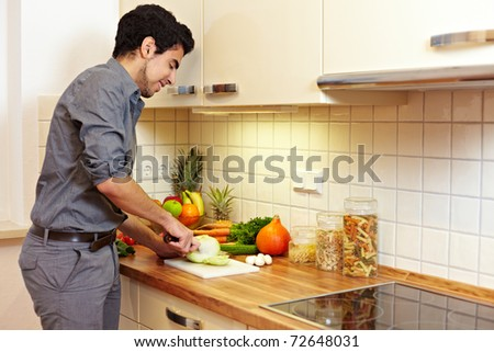 Happy man cutting kohlrabi (Brassica oleracea var. gongylodes L.) on a kitchen counter - stock photo