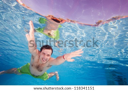 Happy man diving underwater in the pool with wide smile - stock photo