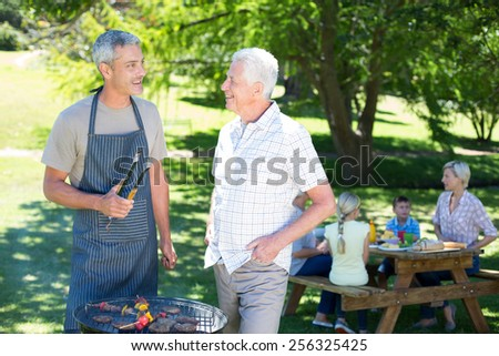 Happy man doing barbecue with his father on a sunny day - stock photo