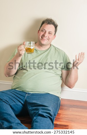 happy man drinking beer sitting on a floor - stock photo
