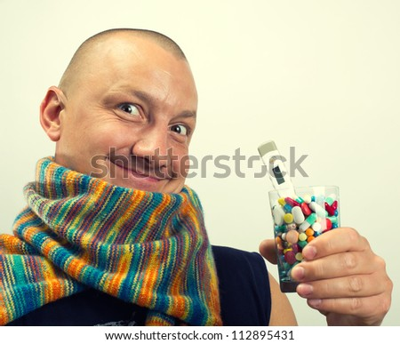 Happy man drinking cocktail of colorful pills - stock photo