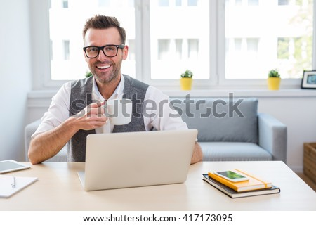 happy man drinking coffee and working on laptop from home - self employment concept - stock photo