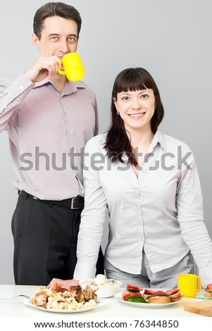 Happy man drinks tea with her woman on kitchen - stock photo