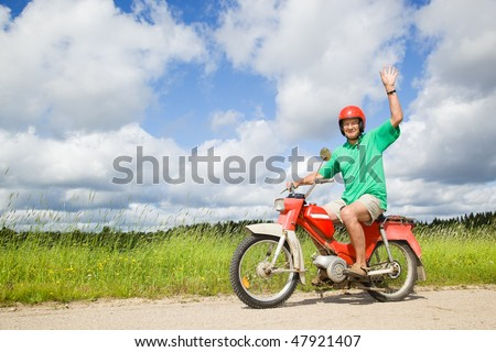 Happy man driving a moped - stock photo