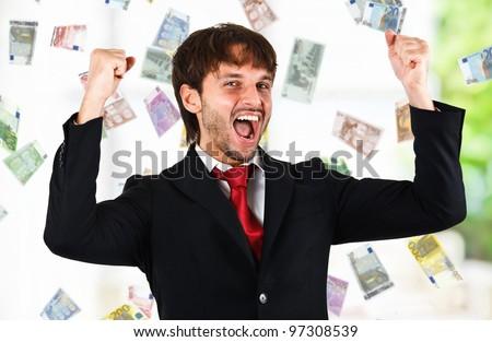 Happy man enjoying a rain of money - stock photo