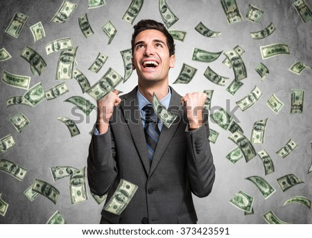 Happy man enjoying the rain of money