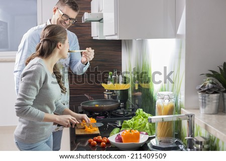 Happy man feeding food to woman cutting vegetables in kitchen - stock photo