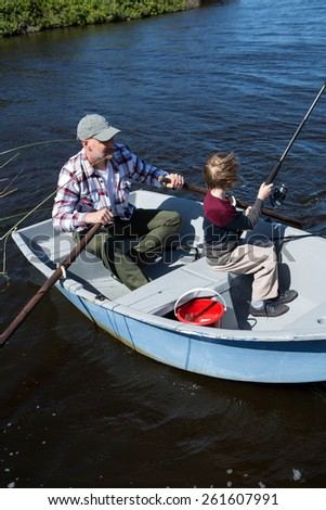 Happy man fishing with his son in the boat - stock photo
