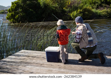 Happy man fishing with his son in the countryside - stock photo