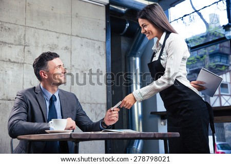 Happy man giving bank card to smiling female waiter in restaurant - stock photo