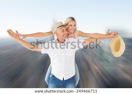Happy man giving his partner a piggy back against city skyline - stock photo
